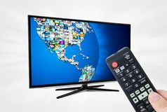 Widescreen high definition TV screen with sphere video gallery. Remote control in hand Stock Image