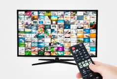 Widescreen high definition TV screen with video gallery. Remote control in hand Royalty Free Stock Image