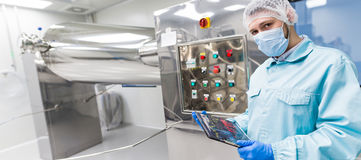 Widescreen picture, factory worker is checking control panel on Royalty Free Stock Image
