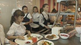 Wideshot-Mädchen in der Schulcafeteria nehmen Platte des Lebensmittels stock video footage