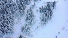 Widoków z lotu ptaka snowboarders na narciarskim dźwignięciu na śnieżnej górze w ośrodku narciarskim i narciarki zdjęcie wideo