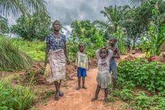 Widok Angolska rodzina, matka z jej trzy dziećmi przed jej małą ziemią uprawną, zdjęcie royalty free