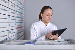 Widok Atrakcyjna farmaceuta bierze notatki przy pracą fotografia royalty free