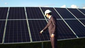 Widok biznesmena odprowadzenie wzdłuż panel słoneczny instalujących w polu zbiory wideo