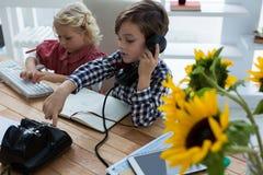 Widok bizneswoman używa komputer w biurze podczas gdy męski kolega opowiada na telefonie Obraz Stock