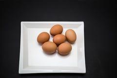 widok brązu gospodarstwa rolnego kurczaka świezi jajka w białego kwadrata eleganckim ceramicznym talerzu Zdjęcia Royalty Free