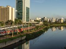 Widok budynki, CPTM pociąg, ruch drogowy pojazdy i rzeka w Brzeżnej Pinheiros rzeki alei, fotografia stock