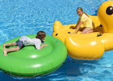 Widok, chłopiec 7 i dziewczyny 11 pławik na ich dużych nadmuchiwanych zwierzętach po środku błękitnego basenu, mnóstwo zabawę fotografia royalty free