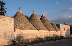 Widok conical suchego kamienia dachy grupa trulli mieści outside Alberobello w Puglia Włochy obrazy stock