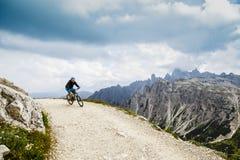 Widok cyklisty jeździecki rower górski na śladzie w dolomitach, Tre C zdjęcie stock