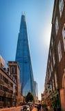 Widok czerep - nowożytny drapacz chmur z swój futurystycznej szklanej strzałkowatej iglicy fasady formularzowy wyłaniać się międz Zdjęcia Stock