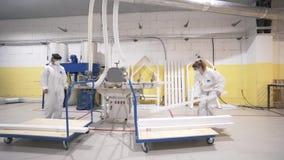 Widok dwa kobiety w białych ochronnych coveralls i maski zbliżamy woodworking maszynę akcja Kobiety skupiać się na pracować zbiory wideo