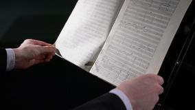 Widok dyrygent otwiera muzyczną książkę i trzyma je zdjęcie wideo