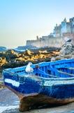 Widok Essaouira fortyfikował miasto i błękitną łódź na plaży Atmosferyczny wizerunek w wieczór świetle z zmierzchu kolorem Obrazy Stock