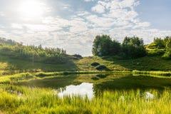 Widok halny jezioro z gładką wodą i odbiciem, iluminujący słońcem przez chmur zdjęcie stock