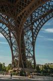 Widok jeden leg's odprasowywa strukturę wieża eifla z niebieskim niebem i światłem słonecznym w Paryż, Zdjęcie Stock