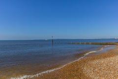 Widok kamienista plaża z groyne falochronem i spokojny morze pod majestatycznym niebieskim niebem zdjęcia royalty free