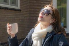 Widok kobieta siedzi w jej ogródzie z jej twarzą przywykającą pierwszy ciepli słońce promienie w wczesnej wiośnie z okularami prz zdjęcie stock