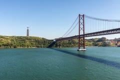 Widok 25 Kwietnia Chrystus i most królewiątko zabytek w Lisbon, Fotografia Royalty Free