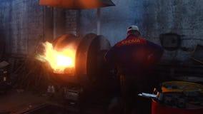 Widok ludzie w coveralls na fabryce pracuje z wyposażeniem dla stalowego wytapiania starej hutniczej roślinie lub zbiory