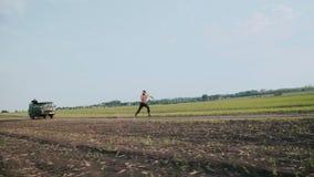 Widok mężczyzna bieg zdala od pojazdu w polach 4K zbiory
