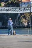 Widok mężczyzny czekanie na Ribeira dokuje z plecakiem na ziemi, rzece i moście, jako tło fotografia royalty free