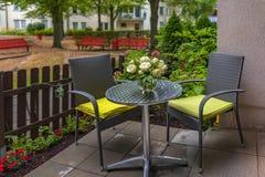 Widok mały taras, część wielki podwórze z dwa szarymi łozinowymi krzesłami z żółtymi poduszkami, obrazy royalty free