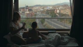 Widok macierzysty lying on the beach na łóżku z małym synem przeciw ogromnemu panoramicznemu okno i pejzażowi miejskiemu, Barcelo zbiory wideo