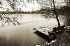 Widok na ławce i footbridge w zimie przyprawiamy w czarny i biały sepiowym, Ljubljana, Slovenia Zdjęcia Stock