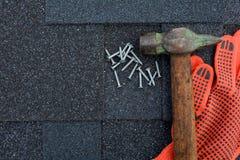 Widok na Asfaltowego dekarstwa gontów tle Dachowi gonty - dekarstwo Asfaltowego dekarstwa gonty młot, rękawiczki i gwoździe, fotografia stock