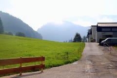 Widok na drodze blisko zielenieć łąkę z domami i górami na tle Fotografia Royalty Free