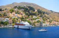 Widok na Greckiego dennego Symi wyspy portu schronienia statku klasycznych jachtach, domy na wysp wzgórzach, turysty morza egejsk Fotografia Royalty Free