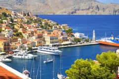 Widok na Greckim dennym Symi wyspy schronienia porcie, klasyczni statków jachty, domy na wysp wzgórzach, turysty morza egejskiego Obraz Stock