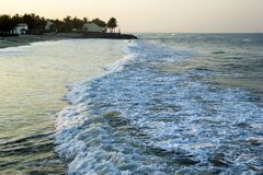Widok na morzu macha z plażowymi domami i drzewkami palmowymi na tle Obraz Royalty Free