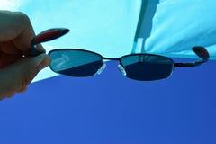Widok na plażowej słońce osłonie i niebieskie nieba przez dioptrycznych okularów przeciwsłonecznych z UV400 filtrujemy Zdjęcia Royalty Free