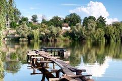Widok na rzece z wiejskimi budynkami i drewnianym mostem kłaść up dalej Obraz Royalty Free