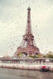 Widok na wieży eifla przez okno z podeszczowymi kroplami Zdjęcie Royalty Free
