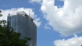 Widok na wielkim szklanym centrum biznesu przeciw tłu poruszające szare chmury spod spodu szklany odbicia zbiory