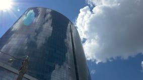 Widok na wielkim szklanym centrum biznesu przeciw tłu poruszające szare chmury spod spodu szklany odbicia zdjęcie wideo