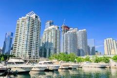Widok nabrzeże parkował jachty i motorowe łodzie z mieszkaniowymi nowożytnymi eleganckimi mieszkanie własnościowe budynkami w tle Obraz Royalty Free