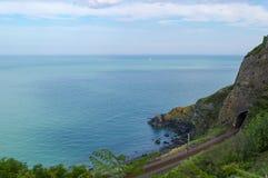 Widok nad Irlandzkim morzem w Wicklow, Irlandia, z sztachetowym tunelem przez falezy w przedpolu obrazy stock