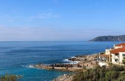 Widok objawienie pańskie ceremonia przy Kardamyli Grecja po księdza rzucał krzyż w oceanie i młodych człowieków od miasteczka h Fotografia Royalty Free