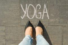Widok od above, żeńscy cieki z teksta joga pisać na popielatym chodniczku obraz royalty free