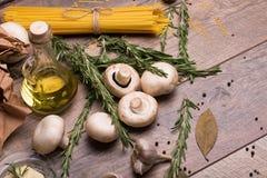 Widok od above na kluskach, pieczarkach, nafcianej butelce, czosnku i rozmarynach, Uncooked składniki na drewnianym stole Zdjęcie Stock