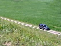 Widok od above samochodowa jazda wzdłuż drogi gruntowej wśród zielonych łąk na słonecznym dniu Odtwarzanie samochodem w naturze fotografia royalty free