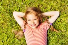 Widok od above uśmiechnięta dziewczyna kłaść na trawie obrazy stock