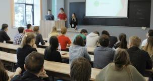 Widok od behind grupa ucznie w sala lekcyjnej, słucha jako ich nauczyciel trzyma wykład widok z powrotem zbiory
