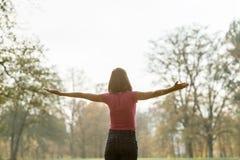 Widok od behind młodej kobiety pozycja w parku z ona ręki Zdjęcia Royalty Free