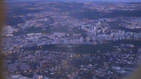 Widok od desantowego samolotu out okno miasto przy zmierzchem zbiory wideo