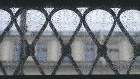 Widok od kropelek nadokiennych na zamazanych ludziach chodzi na ulicie w zwolnionym tempie z parasolami podczas deszczu zbiory